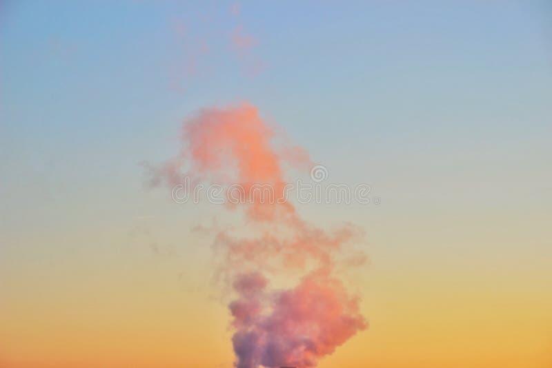 Ιώδες σύννεφο του κάθετου καπνού σε έναν ζωηρόχρωμο ουρανό ηλιοβασιλέματος με μια μετάβαση από το μπλε στο πορτοκάλι στοκ φωτογραφία με δικαίωμα ελεύθερης χρήσης