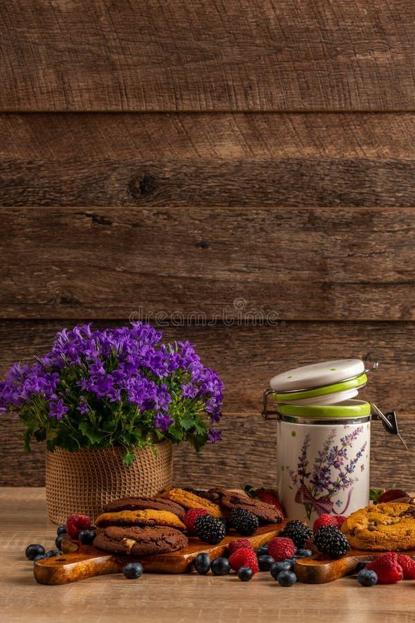 Ιώδες campanula και κεραμικό βάζο με τα μπισκότα και τα άγρια μούρα στο σκοτεινό ξύλινο υπόβαθρο στοκ εικόνα με δικαίωμα ελεύθερης χρήσης