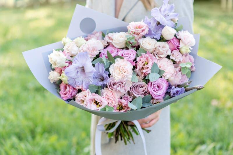 Ιώδης και ρόδινη ανθοδέσμη άνοιξη κρητιδογραφιών όμορφη Νέο κορίτσι που κρατά μια ρύθμιση λουλουδιών με τα διάφορα λουλούδια έξυπ στοκ φωτογραφία