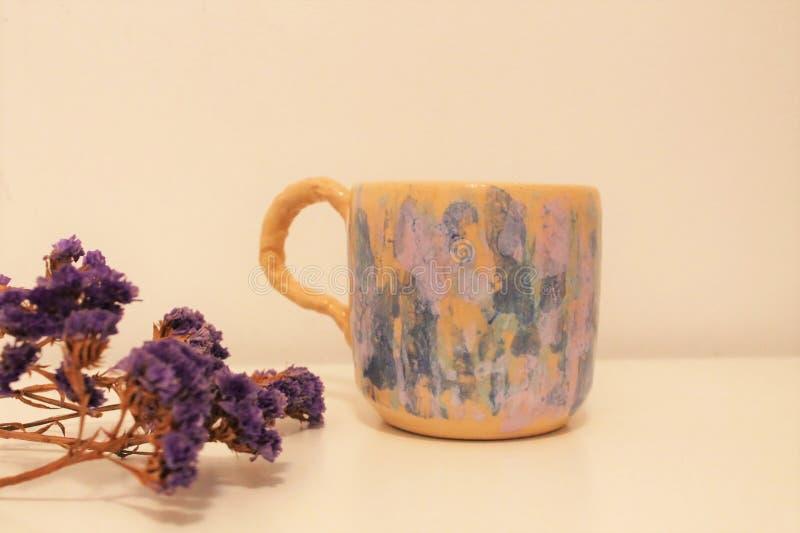 Ιώδη λουλούδια και φλυτζάνι με πολλά χρώματα στοκ εικόνα