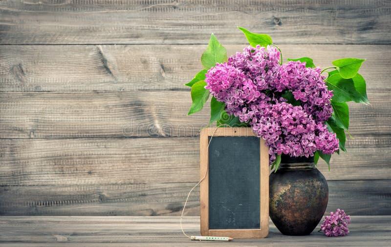 Ιώδη λουλούδια με τον πίνακα στο ξύλινο υπόβαθρο στοκ φωτογραφία με δικαίωμα ελεύθερης χρήσης