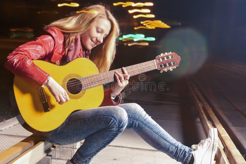 Ιδέες και έννοιες τρόπου ζωής νεολαίας Νεολαίες που χαμογελούν την καυκάσια ξανθή γυναίκα που παίζει την κιθάρα υπαίθρια τη νύχτα στοκ εικόνες