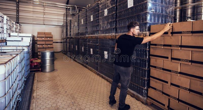 Ιδιοκτήτης ζυθοποιείων που ελέγχει τα κιβώτια μπύρας στο χώρο αποθήκευσης παράδοσης στοκ φωτογραφία με δικαίωμα ελεύθερης χρήσης