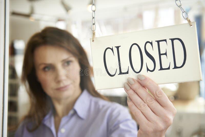 Ιδιοκτήτης καταστημάτων που γυρίζει το κλειστό σημάδι στην πόρτα καταστημάτων στοκ εικόνα