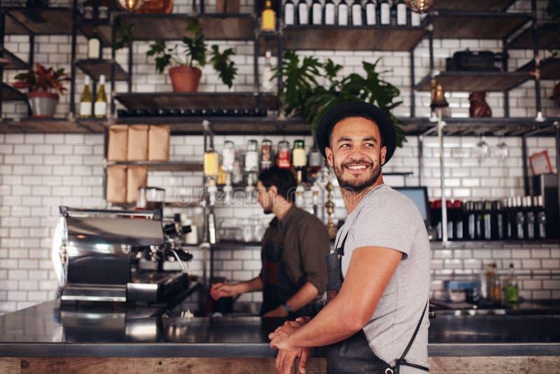 Ιδιοκτήτης καφετεριών με το barista που εργάζεται μέσα πίσω στοκ εικόνες με δικαίωμα ελεύθερης χρήσης