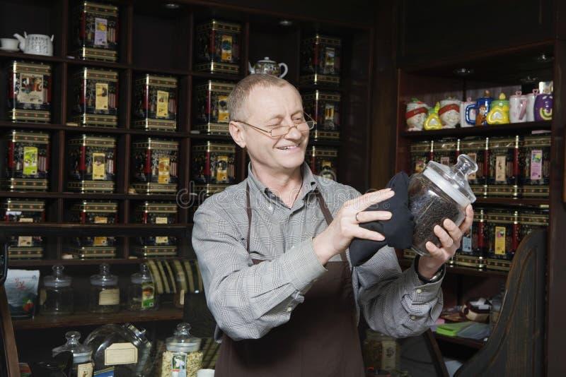 Ιδιοκτήτης που ξεσκονίζει το βάζο του τσαγιού στοκ φωτογραφία