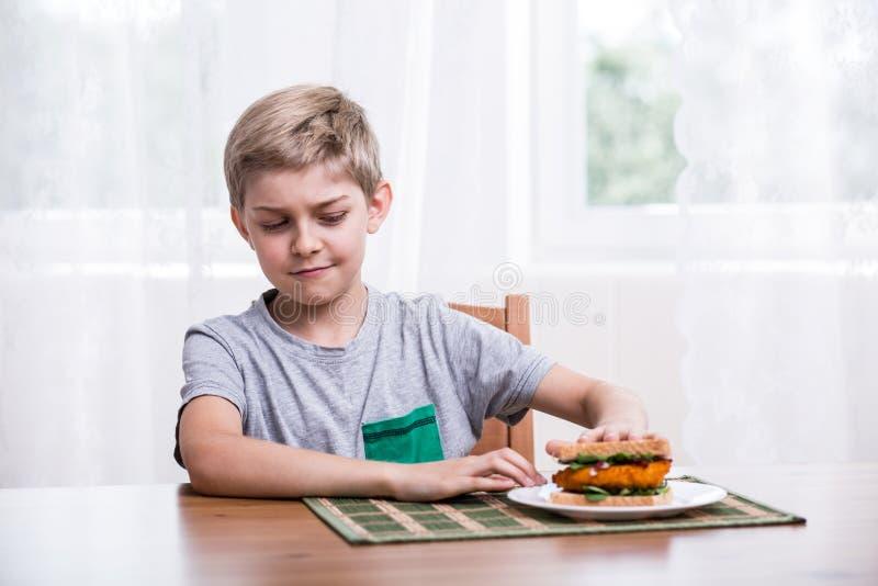 Ιδιότροπο παιδί με το σάντουιτς κοτόπουλου στοκ φωτογραφίες