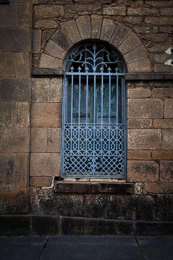 Κάγκελα σιδήρου πέρα από το παλαιό σχηματισμένο αψίδα παράθυρο στοκ φωτογραφία με δικαίωμα ελεύθερης χρήσης