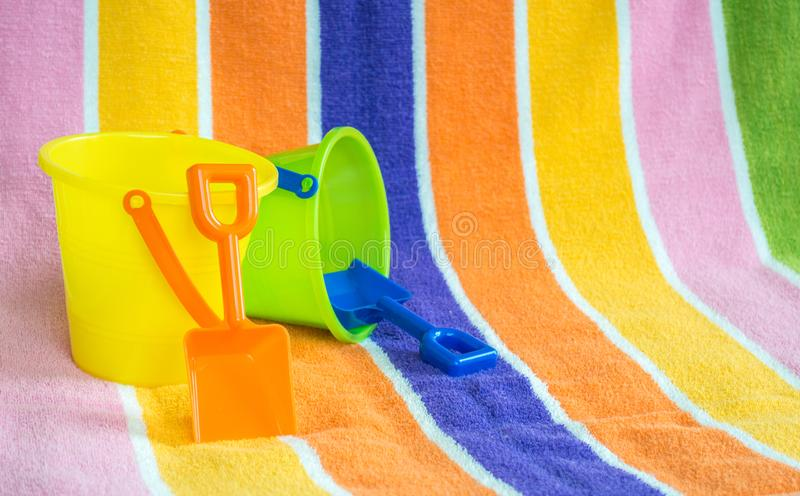 2 κάδοι και φτυάρια παιδιών ` s σε μια πετσέτα παραλιών στοκ φωτογραφία με δικαίωμα ελεύθερης χρήσης