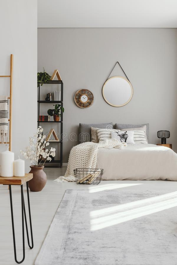 Κάθετη άποψη της κρεβατοκάμαρας ethno με το μεγάλο άνετο κρεβάτι με το μπεζ duvet και τα μαξιλάρια, πραγματική φωτογραφία στοκ φωτογραφία με δικαίωμα ελεύθερης χρήσης