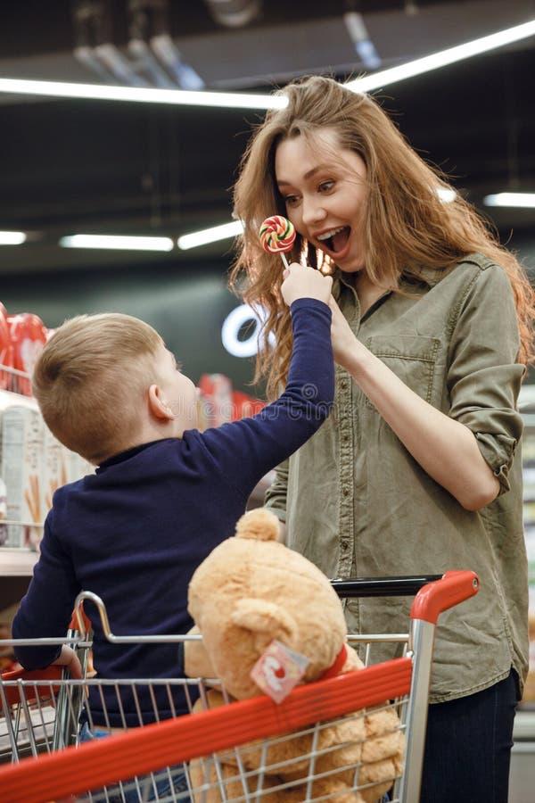 Κάθετη εικόνα του νέου αγοριού που παρουσιάζει καραμέλα στη μητέρα του στοκ εικόνα με δικαίωμα ελεύθερης χρήσης