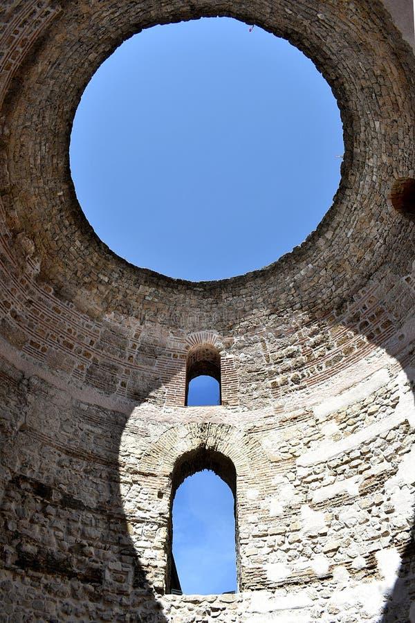 Κάθετη σειρά τριών παραθύρων στον άσπρο τοίχο, με το μπλε ουρανό που λάμπει κατευθείαν στοκ εικόνες