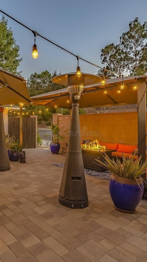 Κάθετη υπαίθρια να δειπνήσει και να καθίσει περιοχή στο άνετο patio πετρών ενός σπιτιού στοκ εικόνα με δικαίωμα ελεύθερης χρήσης