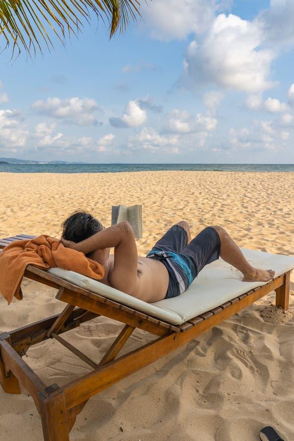 Κάθετη φωτογραφία του ασιατικού ατόμου που κάνει ηλιοθεραπεία και που διαβάζει το βιβλίο στοκ εικόνα