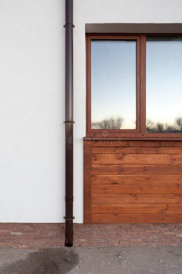 Κάθετη φωτογραφία του μακριού καφετιού σωλήνα υδρορροών βροχής στον άσπρο τοίχο στο νέο άνετο σπίτι με το στοιχείο του ξύλινου πα στοκ φωτογραφίες