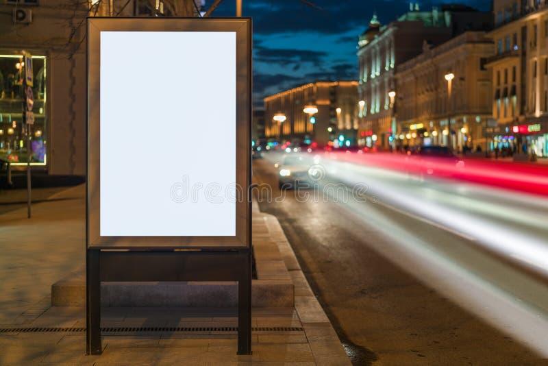 Κάθετος κενός καμμένος πίνακας διαφημίσεων στην οδό πόλεων νύχτας Στα κτήρια και το δρόμο υποβάθρου με τα αυτοκίνητα Χλεύη επάνω στοκ φωτογραφία με δικαίωμα ελεύθερης χρήσης