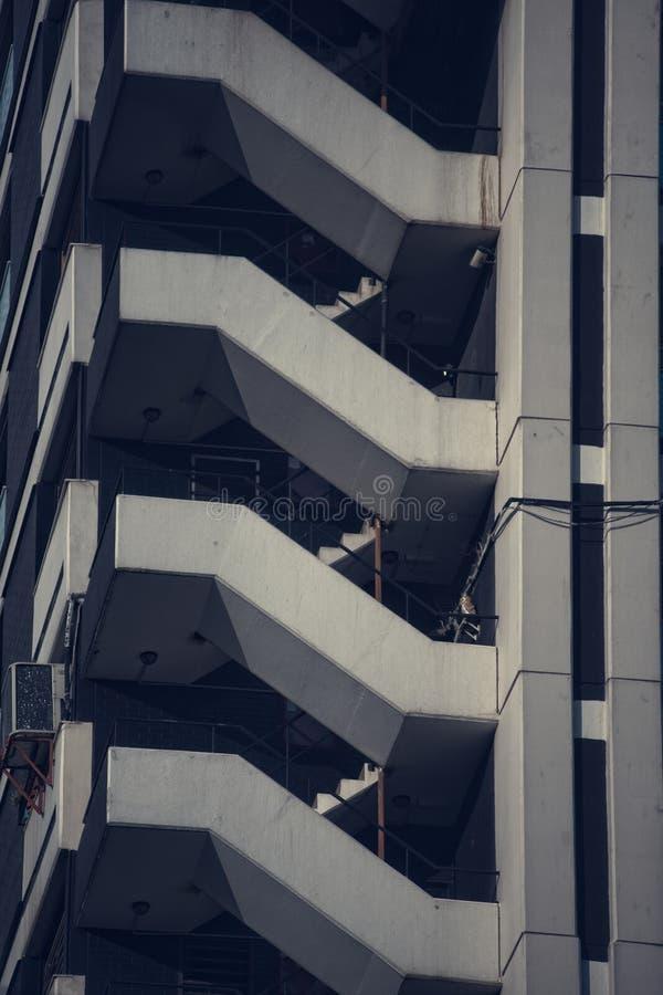 Κάθετος πυροβολισμός κινηματογραφήσεων σε πρώτο πλάνο μιας πλευράς πολυκατοικίας με τη σύγχρονη αρχιτεκτονική στοκ φωτογραφία με δικαίωμα ελεύθερης χρήσης