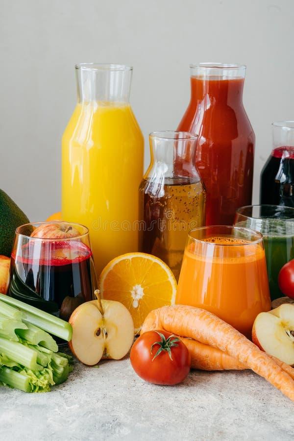 Κάθετος πυροβολισμός του φρέσκου χυμού φρούτων και λαχανικών στα μπουκάλια γυαλιού, διαφορετικά συστατικά, άσπρο υπόβαθρο Υγιής κ στοκ φωτογραφίες