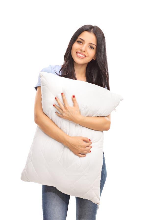 Κάθετος πυροβολισμός μιας νέας γυναίκας που αγκαλιάζει ένα μαξιλάρι στοκ εικόνα με δικαίωμα ελεύθερης χρήσης