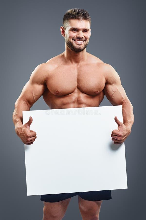 Κάθετο γυμνό μυϊκό άτομο που καλύπτει με ένα έμβλημα στοκ φωτογραφία