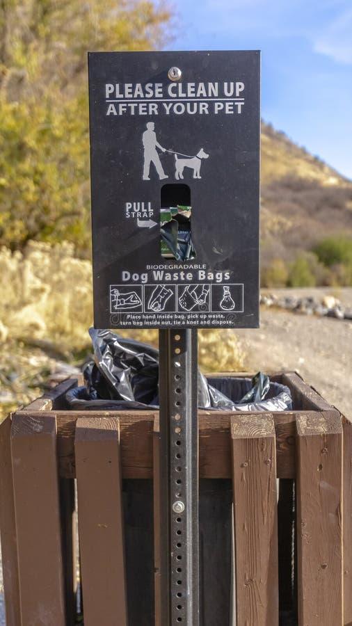 Κάθετο καλάθι αποβλήτων σκυλιών με ένα σημάδι που διαβάζει παρακαλώ καθαρό επάνω μετά από τα κατοικίδια ζώα σας στοκ φωτογραφία