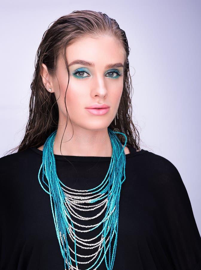 Κάθετο πορτρέτο μιας νέας γυναίκας στο Μαύρο Υγρή τρίχα και επαγγελματικό makeup στοκ εικόνες