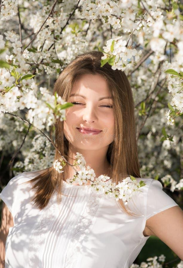 Κάθετο πορτρέτο μιας νέας ελκυστικής γυναίκας στον ανθισμένο κήπο Χαμόγελο με τις προσοχές της ιδιαίτερες στοκ εικόνες
