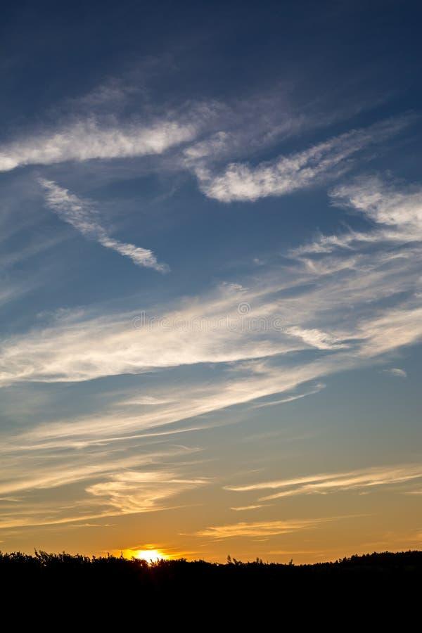 Κάθετο cloudscape των βαλμένων σε στρώσεις σύννεφων στο ηλιοβασίλεμα με τον ήλιο στοκ εικόνες