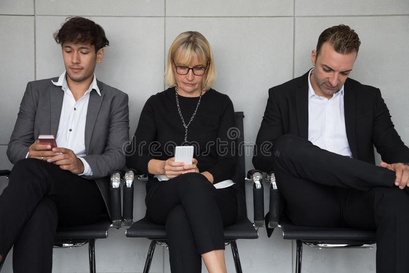 Κάθισμα ανθρώπων περιμένοντας μια συνέντευξη εργασίας και χρησιμοποιώντας την κοινωνική εφαρμογή μέσων στο κινητό τηλέφωνο στοκ εικόνα