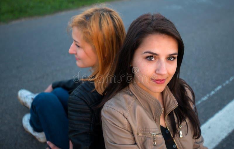 Κάθισμα δύο κοριτσιών πλάτη με πλάτη στοκ φωτογραφίες