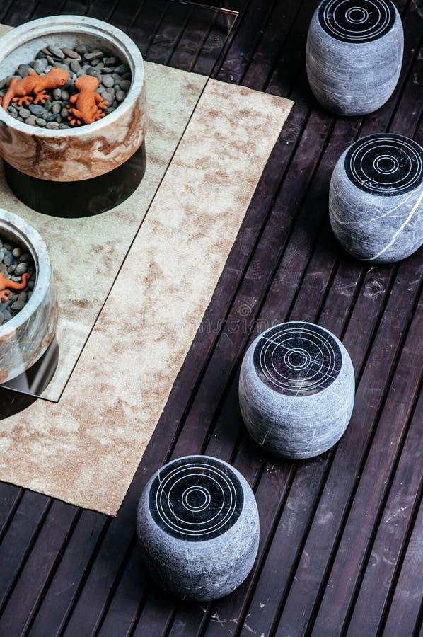 Κάθισμα σκαμνιών πετρών σύγχρονου σχεδίου και πίνακας γυαλιού στο ξύλινο balcon στοκ φωτογραφίες