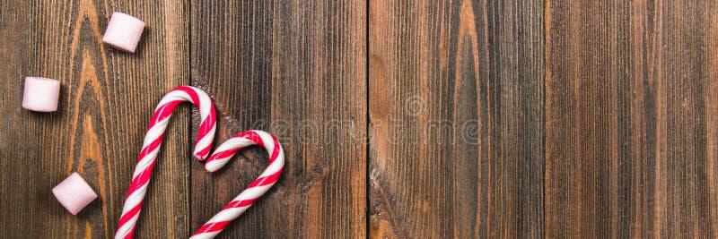 Κάλαμοι καραμελών Χριστουγέννων με μορφή μιας καρδιάς σε έναν καφετή ξύλινο πίνακα διάστημα αντιγράφων Κενό διάστημα δεξιά των αν στοκ εικόνα με δικαίωμα ελεύθερης χρήσης