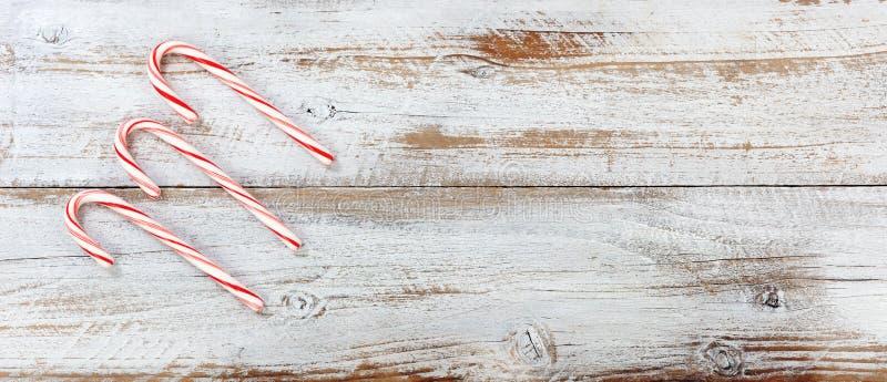 Κάλαμοι καραμελών Χριστουγέννων στο άσπρο αγροτικό ξύλινο υπόβαθρο στοκ εικόνα με δικαίωμα ελεύθερης χρήσης