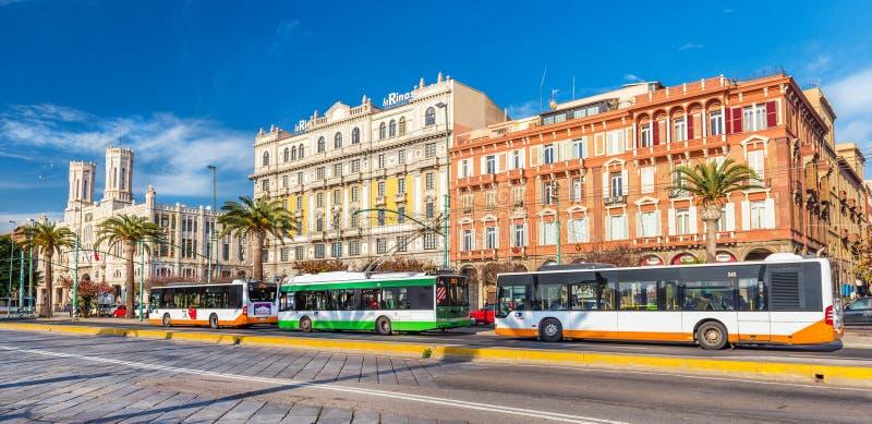 Κάλιαρι, Ιταλία: Λεωφορεία και αυτοκίνητο καροτσακιών που σταθμεύουν κοντά στη στάση λεωφορείου στην κεντρική οδό της πόλης στοκ εικόνα με δικαίωμα ελεύθερης χρήσης