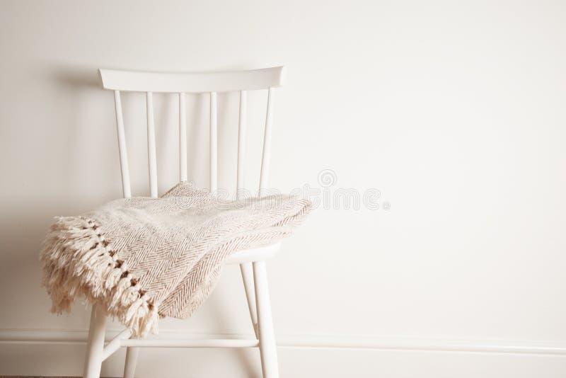 Κάλυμμα ή κάλυμμα στην άσπρη εκλεκτής ποιότητας καρέκλα, minimalistic ύφος οικοκυρική διάστημα αντιγράφων στοκ εικόνες