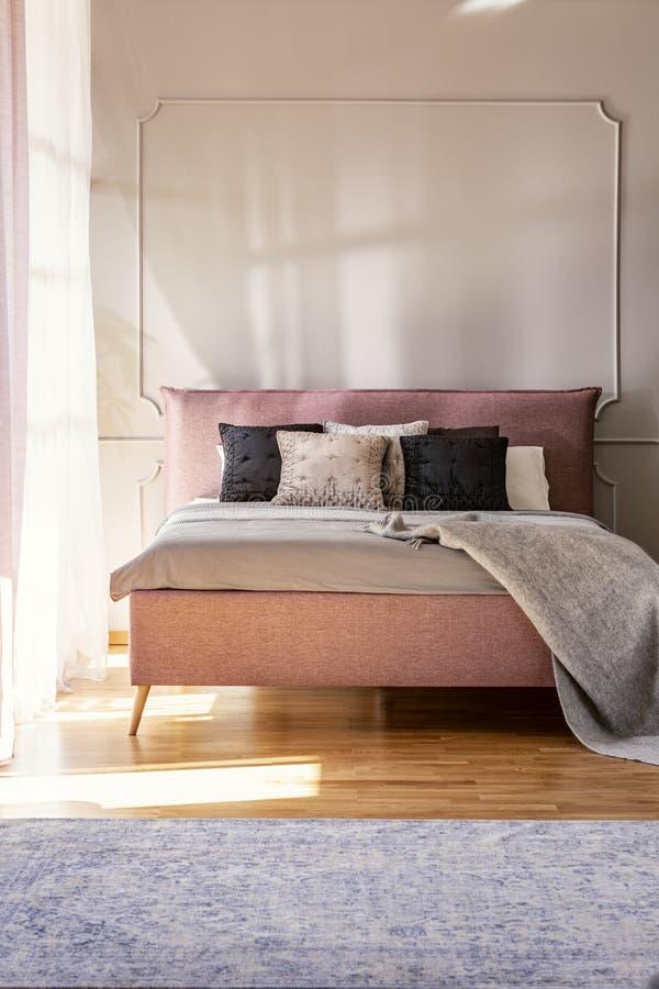 Κάλυμμα και μαξιλάρια στο ρόδινο κρεβάτι στο απλό εσωτερικό κρεβατοκάμαρων με τον τάπητα και τον τοίχο με τη σχηματοποίηση Πραγμα στοκ φωτογραφία με δικαίωμα ελεύθερης χρήσης