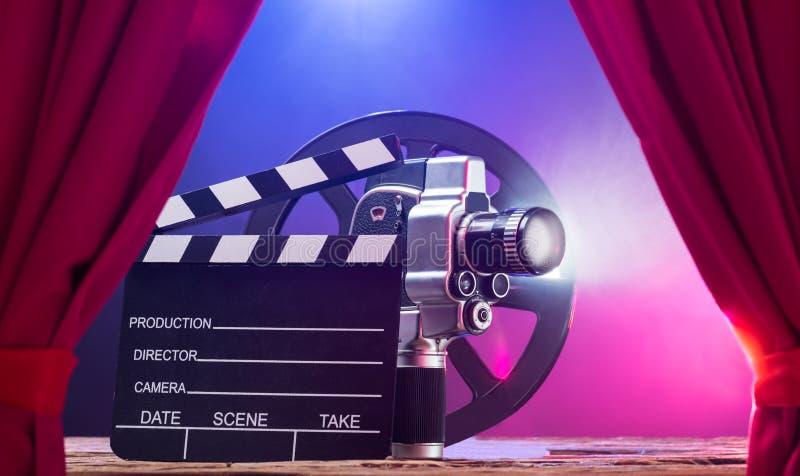 Κάμερα κινηματογράφων με Clapperboard και εξέλικτρο ταινιών στη σκηνή στοκ φωτογραφία με δικαίωμα ελεύθερης χρήσης