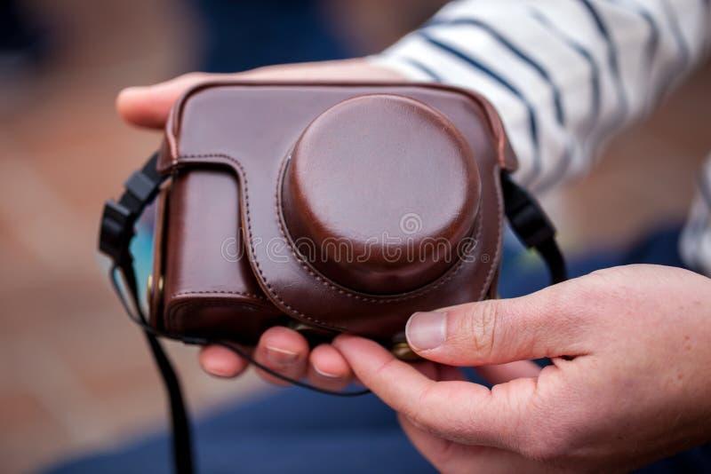 Κάμερα λαβής χεριών ατόμων σε μια κομψή και μοντέρνη περίπτωση δέρματος στοκ εικόνα με δικαίωμα ελεύθερης χρήσης