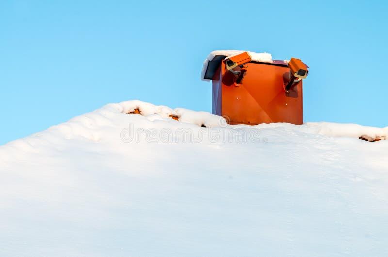 Κάμερα παρακολούθησης σε μια χιονώδη στέγη στοκ φωτογραφίες
