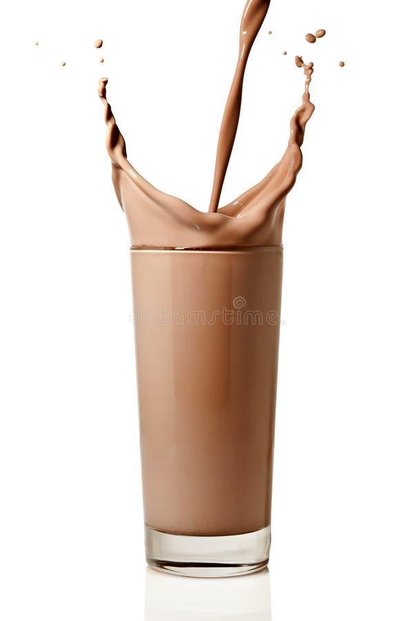 Κάνοντας έναν παφλασμό με την έκχυση του γάλακτος σοκολάτας σε ένα γυαλί στοκ φωτογραφία με δικαίωμα ελεύθερης χρήσης