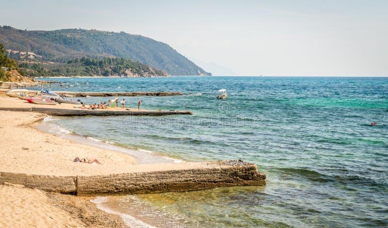Κάνοντας ηλιοθεραπεία στην παραλία σε Ouranoupoli, Ελλάδα στοκ εικόνες