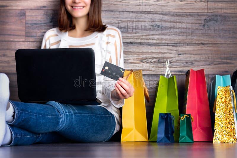 Κάνοντας πληρωμή αγοράς χαμόγελου γυναικών θηλυκή ενήλικη στο σε απευθείας σύνδεση κατάστημα καταστημάτων Διαδικτύου υφασμάτων μό στοκ εικόνα