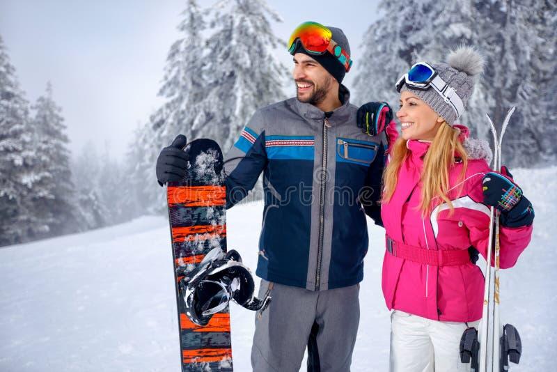 Κάνοντας σκι και snowboarding απόλαυση χαμογελώντας ζευγών στο χιονώδες mountai στοκ φωτογραφία με δικαίωμα ελεύθερης χρήσης
