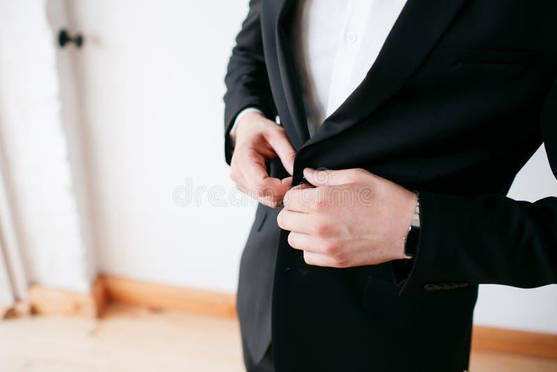 Κάνοντας την επιχείρηση να φανεί καλή Κινηματογράφηση σε πρώτο πλάνο του ατόμου που κουμπώνει το σακάκι του στεμένος στο άσπρο κλ στοκ φωτογραφία με δικαίωμα ελεύθερης χρήσης
