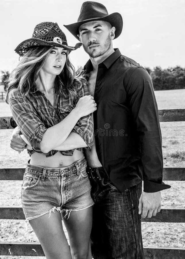 Κάουμποϋ και cowgirl στην αγροτική πάλη αγροκτημάτων δίπλα στο ξύλινους πρόσωπο και τους τομείς στοκ εικόνες