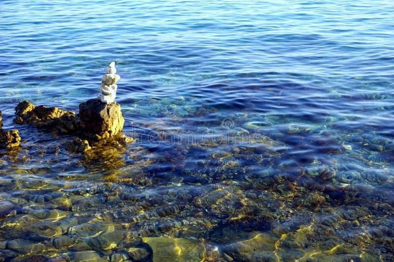 Κάποια άσπρη πέτρα που συσσωρεύεται στο σαφές μπλε θαλάσσιο νερό στοκ εικόνες με δικαίωμα ελεύθερης χρήσης