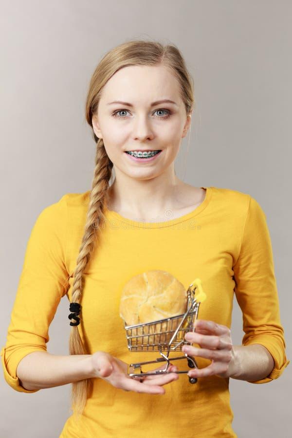 Κάρρο αγορών εκμετάλλευσης γυναικών με το ψωμί στοκ φωτογραφία με δικαίωμα ελεύθερης χρήσης