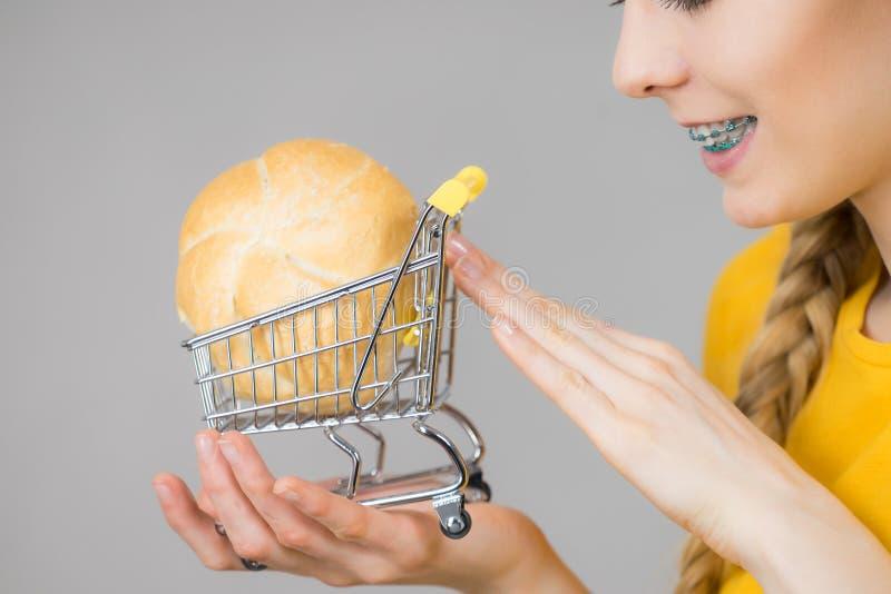 Κάρρο αγορών εκμετάλλευσης γυναικών με το ψωμί στοκ φωτογραφίες με δικαίωμα ελεύθερης χρήσης