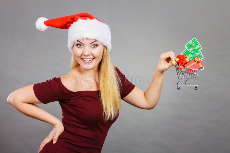 Κάρρο αγορών εκμετάλλευσης γυναικών Santa με τα δώρα Χριστουγέννων στοκ εικόνα
