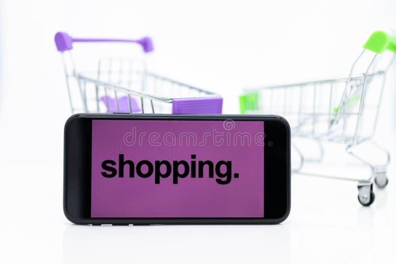 Κάρρο αγορών και έξυπνο τηλέφωνο, χρήση εικόνας για τη λιανική επιχείρηση on-line για την υποστήριξη του πελάτη στο διαδίκτυο, επ στοκ εικόνα